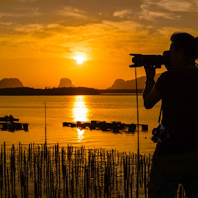 Photographer taking the sunrise  by Waraphorn Aphai - People Portraits of Men ( sam chong, shadow, silhouette, camera, phang nga, vibrant sky, thailand, photographer, sunrise, fisherman, boat,  )