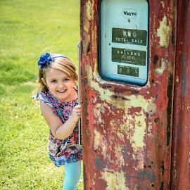Peeking Around The Old Gas Pump by T Sco - Babies & Children Child Portraits ( child, gas, girl, grass, summer, pump, antique, outside, portrait, kid )