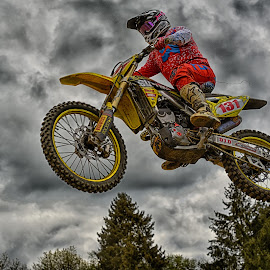 by Marco Bertamé - Sports & Fitness Motorsports ( clouds, flying, red, motocross, speed, grey, air, high, race, noise, jump )