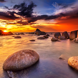 Golden light on rock beach by Dany Fachry - Landscapes Beaches