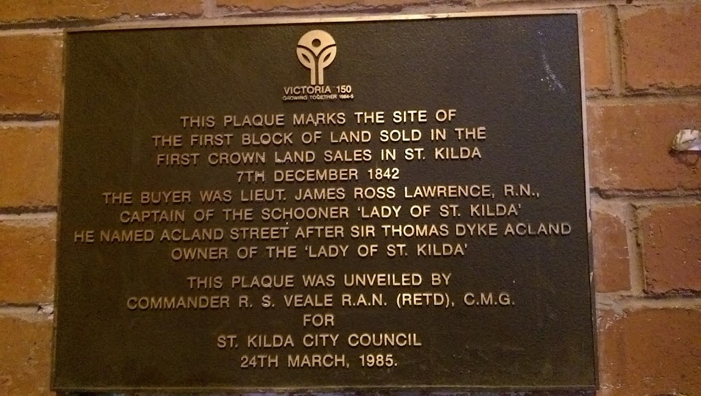 On the side wall of a St Kilda Convenience Store in Ackland Street. Erected as part of Victoria's 150 year anniversary.  It is headed by the logo for the event. Plaque Reads: Victoria 150 Growing ...