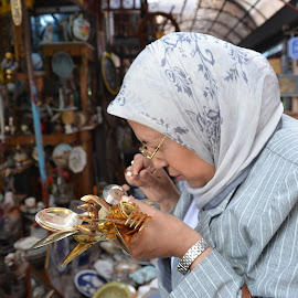 Woman examining flatware in Athens by Bill Frank - People Street & Candids ( market, greece, athens, shopping, travel, travel photography, travel locations )