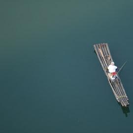 LONE RAFT by Zac Rushbrook - People Street & Candids ( blue, bamboo raft, candid, fishing, carm )