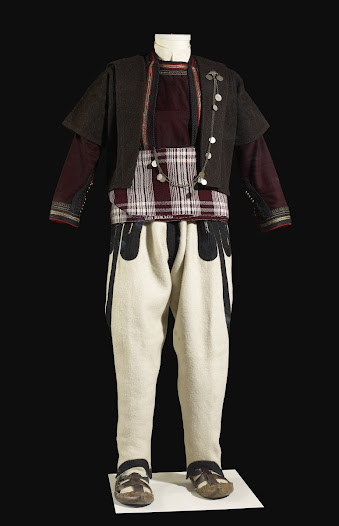 <b>Man's wedding costume</b>  This costume was acquired by the donor from the widow of the man who wore it for their wedding in 1910. The dark red under-jacket has an inner flap across the front and is decorated with metal-thread braiding.