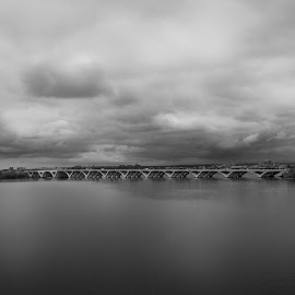Bridge to DC by Brianne Toma - Black & White Buildings & Architecture ( sky, district of columbia, wide angle, maryland, national harbor, distant, clouds, waterscape, far, monochrome, cinematic, far away, bridge, virginia, black and white, washington, woodrow wilson bridge, dc, architecture,  )