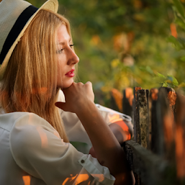 Looking over the fence by Sabin Malisevschi - People Portraits of Women ( fence, blonde, wooden, warm, girl, sunset, beautiful, nice, summer, evening, rural, hat )