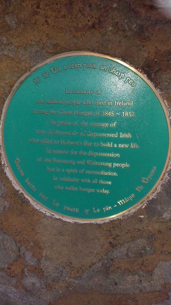 Plaque on a large bluestone rock: 'In memory of one million people who died in Ireland during the Great Hunger of 1845-52. In praise of tens of thousands of dispossessed Irish who sailed to Hobson`s ...
