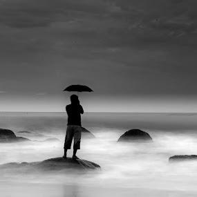 A long wait. . . . . . .  by Sudharshun Gopalan - People Portraits of Men ( loneliness, gopalan, umbrella, d7000, sudharshun, long exposure, beach, wait, alone )