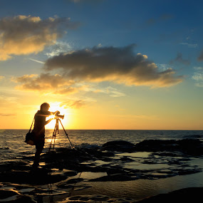 Silhouette shot of a photographer at sunset. Taken at the Tip of Borneo, Borneo, Sabah, Malaysia. by Macbrian Mun - Landscapes Sunsets & Sunrises ( cameraman, person, single, silhouette, shine, rock, yellow, travel, beach, people, borneo, sabah, backlit, sky, nature, autumn, shadow, dark, sunshine, light, alone, black, orange, wallpaper, twilight, hobby, horizon, malaysia, sunlight, professional, dusk, vacation, backlight, outdoors, scene, view, natural, outside, golden, colorful, moment, vivid, ocean, beauty, landscape, sun, coast, dramatic, asia, men, rocks, evening, man, water, male, beautiful, sea, seascape, scenic, taking, human, red, lighting, color, blue, sunset, outdoor, background, sundown, cloud, summer, scenery, sunrise, standing )