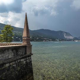 Watching the storm far away by Luca Foscili - Landscapes Weather ( water, clouds, isole borromee, beautiful, lake, architecture, beauty, storm, landscape, transparence, italia, nature, lago maggiore, woman, outdoors, pinnacle, trees, isola bella, light, italy )