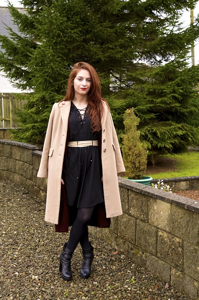 blogger in cutout black dress and camel coat