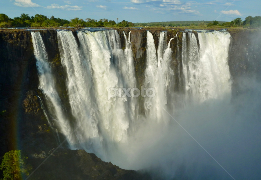 Victoria Falls by Leigh Thomson - Travel Locations Landmarks ( water, zimbabwe, waterfalls, waterscape, trade, victoria falls, tourism, postcard, landscape, landmark, falls, zambia, africa, mist )