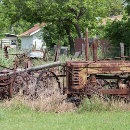 Tractor and the boneyard by Kathy Psencik - Novices Only Street & Candid ( old tractor, farm equipment, rusty tractor, no tires, tractor, farmer relics )