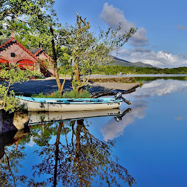 Reflections at the boathouse by Nik Hall - Landscapes Waterscapes ( boating, clouds, reflection, ireland, blue sky, killarney, boathouse, reflections, trees, lake, boat )