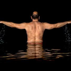 A man standing inside the water and spreads his arms by Markus Gann - People Portraits of Men ( muscular, activity, caucasian, back, summer, swimming, beautiful, view, drops, white, copy space, dark, vacation, bald, model, man, resort, leisure, falling, reflection, relax, wet, night, pool, black, active, swimmer, portrait, water, people, lifestyle, spread, outdoor, standing, enjoyment, ocean, light, healthy, person, background, style, adult, lake, male, swim )