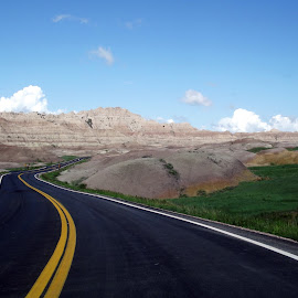 Road Through the Badlands, South Dakota, USA by Jo Brockberg - Transportation Roads ( clouds, lands, hills, highway, grass, driving, sandstone, travel, road, bad, landscape, ancient, blue sky, blacktop, formations, outdoor, path, rocks, daylight, pavement )