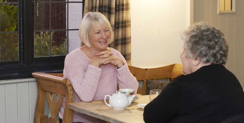 Carer and client talking over a cup of tea