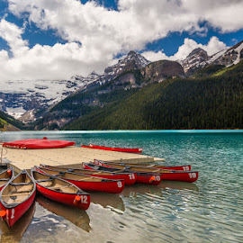 Red Canoes on Lake Louise by Tracy Munson - Transportation Boats ( clouds, lake louise, canada, alberta, rocky mountains, boats, the rockies, tourism, travel, aquamarine, landscape, banff, canoes, dock, turqouise, glacier, mountains, national park, sky, red, nature, canadian, glacial lake, ab, peaks )