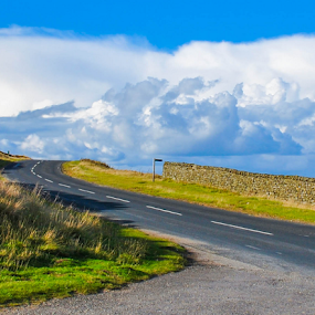 Lonely Road on the North Yorkshire Moors by Del Candler - Landscapes Cloud Formations ( north yorkshire moors, clouds, blue sky, treeless, highway, yorkshire, stonewall, green, moors, lonely,  )