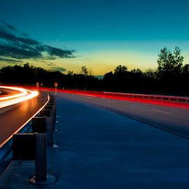 light trails at sunset by David Kreutzer - Transportation Roads ( median, guard rail, cars, sunset, car trails, light trails, road, high way, roadway )
