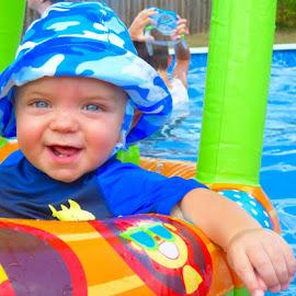 Eyes as blue as the water . by Nita Andrews - Babies & Children Babies ( hand, water, pool, blue, floaty, blue eyes, baby, smile, blue hat, float, swimming, eyes, KidsOfSummer )