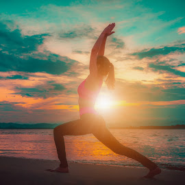 Silhouette young woman practicing yoga on the beach at sunset. V by Nuttawut Uttamaharach - Sports & Fitness Fitness ( calm, body, person, reflection, relax, fitness, silhouette, one, exercise, ocean, beach, people, sun, pose, balance, sky, girl, life, nature, practicing, woman, lifestyle, spirituality, harmony, mind, water, sea, relaxation, morning, health, young, female, sunset, outdoors, peace, healthy, meditation, sunrise, tranquility, yoga )
