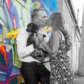 Kissing against a graffiti wall by Justin Duff - People Couples ( dachshund (smooth haired), kissing, selective color, colorful, attractive, graffiti, blond, couple, detroit, dog, wall, engagement )