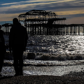 Watching The Sun Setting Over The West Pier by Corin Spinks - People Couples ( brighton, ruin, sunset, silhouette, sea, pier, couple, people,  )