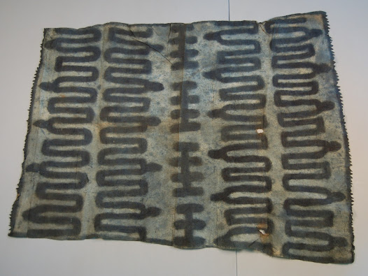 Cloths like this were used to convey local knowledge and customs. The serpentine design on this cloth was described by Solomon Islander Reuben Lilo as related to the highs and lows of life, particularly sickness and death. The dots represent resting places on a journey through mountainous terrain.  Although the barkcloth itself was made by women, only men could paint the images, known collectively as <i>kineha</i>.