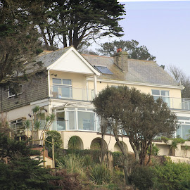 House overlooking Seaton beach, Cornwall. by Nick Stewart - Buildings & Architecture Homes ( hill, stylish, trees, sea, yellow, house, garden )