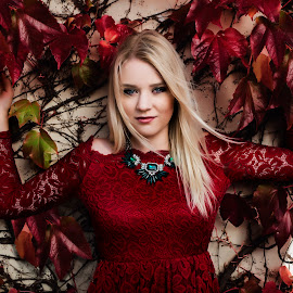 between the ivy by Mirko Webster - People Portraits of Women ( contrast, blonde, red, gorgeous, texture, jewelry, ivy, emerladnecklace, stunning, red dress, wall )