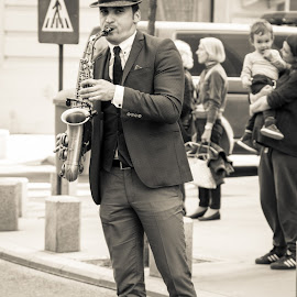 Street saxophone musician by Natalia Dobrescu - People Musicians & Entertainers ( explore, europe, monochrome, street, romania, travel, people, white and black, street photography, city, bucharest, street music, saxophone, musician )