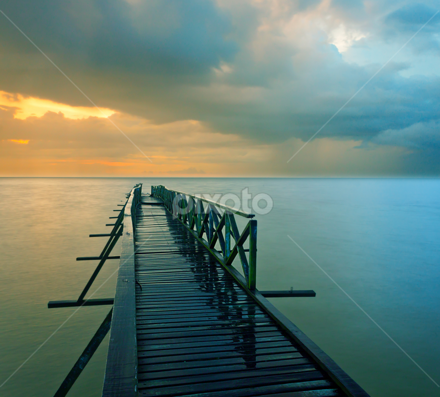 Cloudy and colorful sunset by Macbrian Mun - Landscapes Waterscapes ( stormy, colorful, ocean, jetty, travel, beach, beauty, coastline, landscape, sun, coast, sky, nature, dramatic, cloudy, weather, pier, evening, clouds, water, orange, peaceful, twilight, beautiful, sea, horizon, malaysia, seascape, scenic, sunlight, red, vacation, johore, color, sunset, background, outdoor, cloud, summer, scene, view, golden )