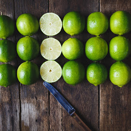 Green lemons and knife by TaTu Thai - Food & Drink Fruits & Vegetables ( plant, raw, old, bamboo, weight, wood, stilllife, diet, paper, slices, tropical, vietnamese, rustic, lowkey, asian, farm, fresh, care, dark, asia, light, knife, fruit, green, art, vietnam, farming, lose, pure, nutrition, food, background, basket, healthy, vitamin, natural, lemon )