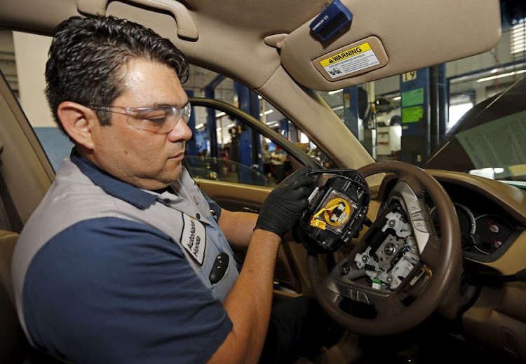 ROCKY ROAD: Technician Edward Bonilla holds a recalled Takata air bag inflator after he removed it from a Honda Pilo. Picture: REUTERS