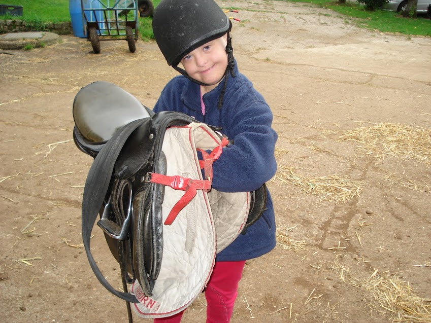 A young rider helping to tack up