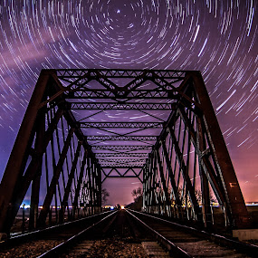 Tracks Underneath the Train by Eric Anderson - Buildings & Architecture Bridges & Suspended Structures ( omaha, clouds, iowa, structure, railroad, tracks, time, lapse, stars, trail, night, bridge, nebraska, river )