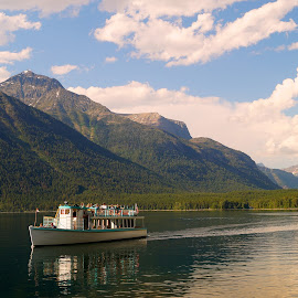 Cruising by Beth Collins - Transportation Boats ( water, clouds, mountain, park, waterscape, national, historic boat, lake, boat, sight seeing, historic, boating, site seeing, history, national park, mountains, blue sky, lake mcdonald, tourists, desmet, glacier national park, sightseeing )