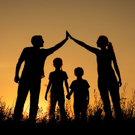 Happy family standing in the park. by Tatiana Kostareva - People Family ( parent, hands, friendship, dad, happy, mother, beautiful, son, trip, day, having, active, girl, field, outside, silhouette, playing, adult, daughter, child, love, sunrise, woman, young, father, kid, boy, sun, holiday, summer, freedom, happiness, joy, walking, grass, vacation, man, leisure, together, park, nature, people, lifestyle, home, outdoor, healthy, sunset, family, travel, fun )