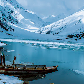 boat in mountains by Umair Khan - Landscapes Mountains & Hills ( clouds, mountains, freeze, snow, lake, landscape, boat )