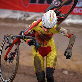 Running With My Machine by Marco Bertamé - Sports & Fitness Cycling ( uphill, mud, red, wheel, bicylcle, woman, shoulder, determined, brown, yellow, helmet, running )