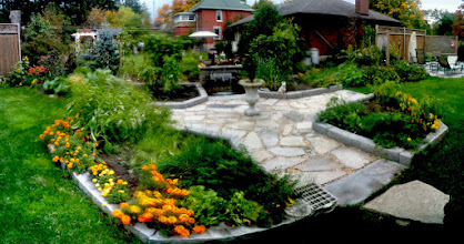 Photo: A formal veggie garden with natural stone curbing and limestone flag. A stone waterfall add sound and motion to the landscape.