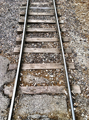 train tracks gravel worn asphalt stock photo