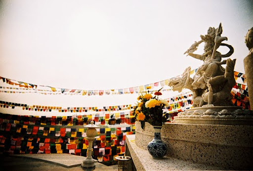 White Dzambhala statue with sea of prayer flags, Rinchen Jangsem Ling, Malaysia, October 9, 2011. Photo by Sue Ngee.