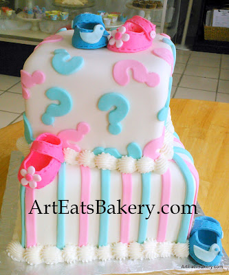 Baby gender reveal cake with question marks, stripes, girl's pink flower booties and boy's blue duck booties
