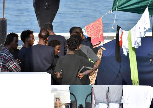 Migrants aboard the Italian Coast Guard ship Diciotti talk as they await decisions in the port of Catania, Italy, Friday, 24 August 2018. An Italian lawmaker says rescued migrants stuck aboard an Italian coast guard ship are starting a hunger strike. Rescued on 16 August 2018 in the Mediterranean Sea, 150 migrants are still on the ship after minors and the sick were allowed off in recent days. Photo: Orietta Scardino / ANSA / AP