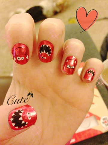 A hand with red nose day nail wraps on the nails