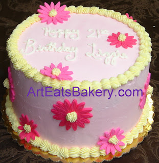 Pink butter cream birthday cake with fondant daises and yellow boarder