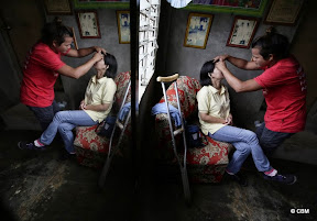 A woman at a beauty salon. A crutch is also in shot.