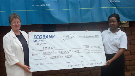 At left, Tracy Beedy from the World Agroforestry Centre (ICRAF) receives a cheque from Ecobank Malawi's Duwa Mkona (right).
